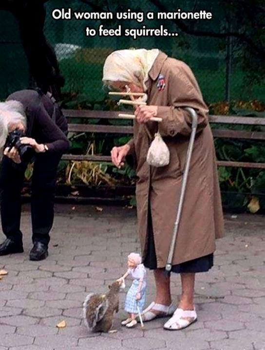 old woman feeding squirrels with puppet